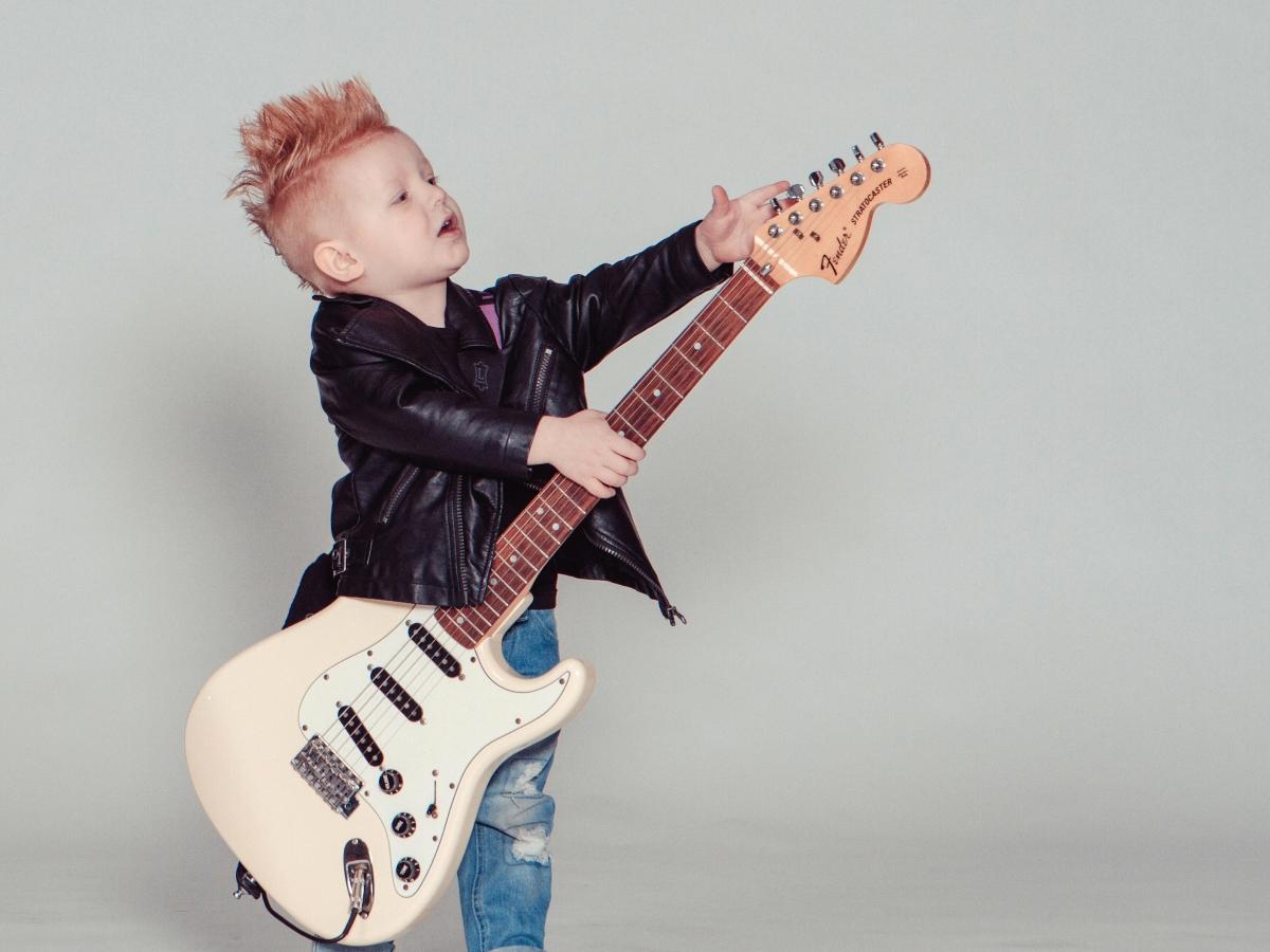 niño aprendiendo a tocar guitarra electrica